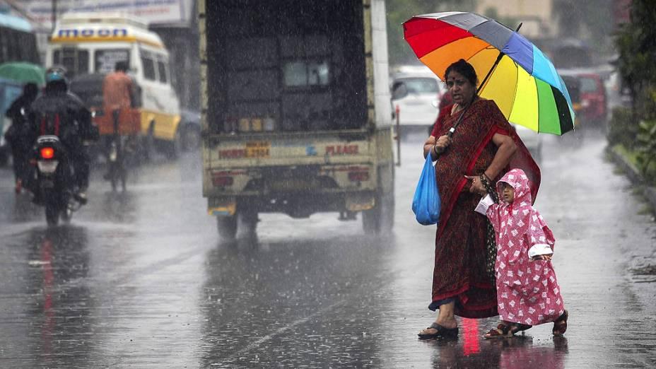 Mulher e sua filha atravessam uma estrada durante chuva de monções em Mumbai, na Índia