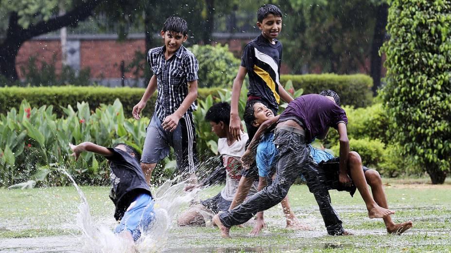 Crianças brincam na chuva em Nova Délhi, na Índia