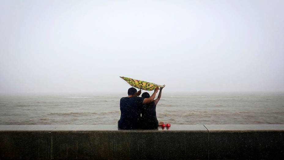 Casal tenta segurar o guarda-chuva virado do avesso em frente em uma praia na costa do Mar Arábico, em Mumbai, na Índia