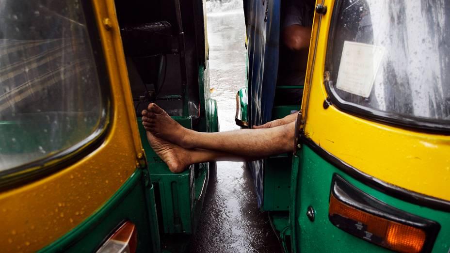 Homem descansa em seu riquixá durante um dia de chuva em Nova Délhi, Índia