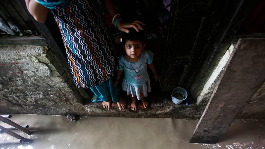 Criança olha enquanto da porta de sua casa inundada devido à cheia do rio Yamuna, na Índia