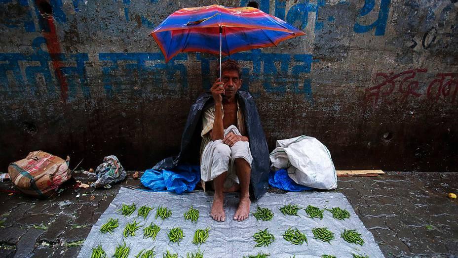 Vendedor de legumes se protege da chuva sentado sobre a lona de um mercado durante as chuvas de monções em Mumbai, na Índia