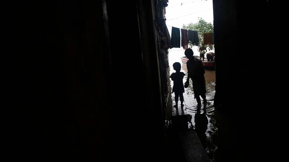 Crianças observam a cheia do rio Yamuna após as fortes chuvas de monção em Nova Délhi, na Índia