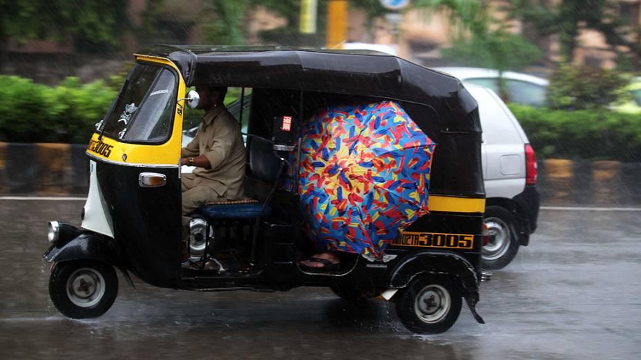 Pessoas se protegem das chuvas dentro de um riquixá em Mumbai, na Índia