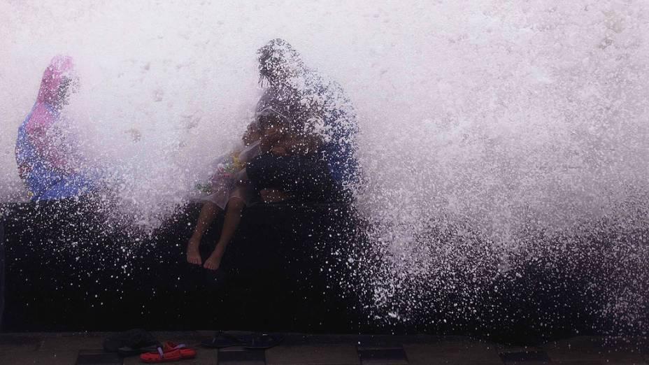 Crianças brincam aproveitando a maré alta em Worli Sea Face, na Índia