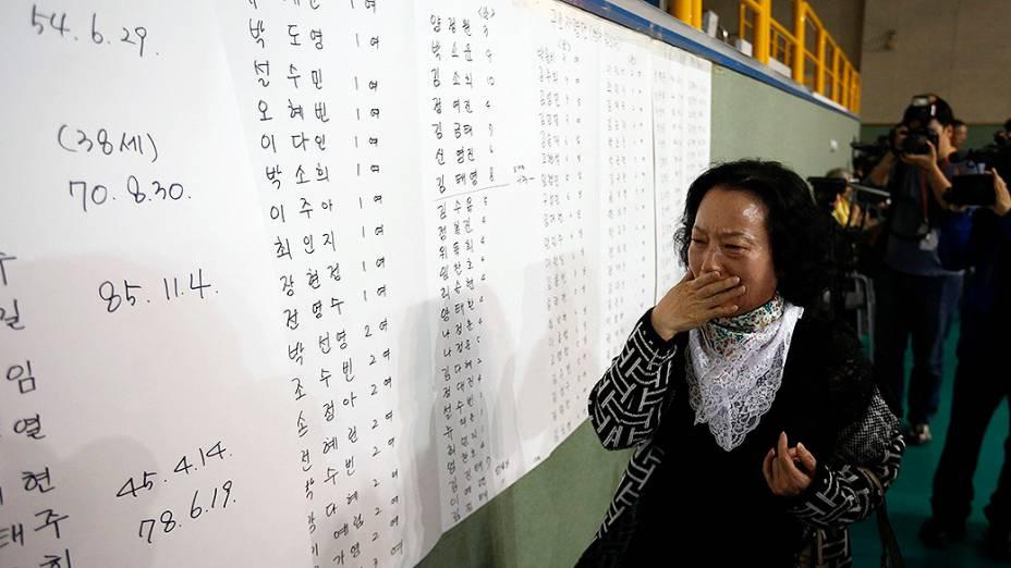 Mãe de um dos passageiros do navio que naufragou próximo a Jindo, na Coreia do Sul se emociona ao encontrar o nome do filho na lista de sobreviventes