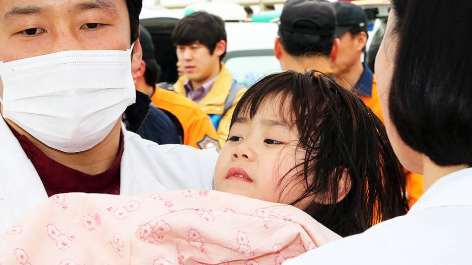 Menina é resgatada do navio Sewol que transportava cerca de 470 pessoas e naufragou na Coreia do Sul