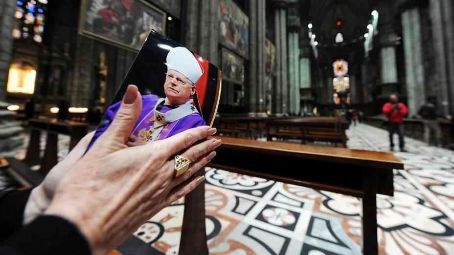 Mulher faz orações com uma fotografia do cardeal Angelo Scola na Catedral de Milão, Itália
