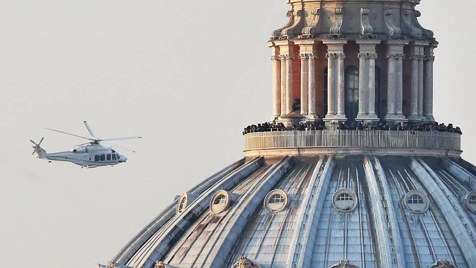 Pessoas lotam a galeria em cima da Basílica de São Pedro no momento em que o helicóptero que transportava o Papa Bento XVI passa em seu caminho