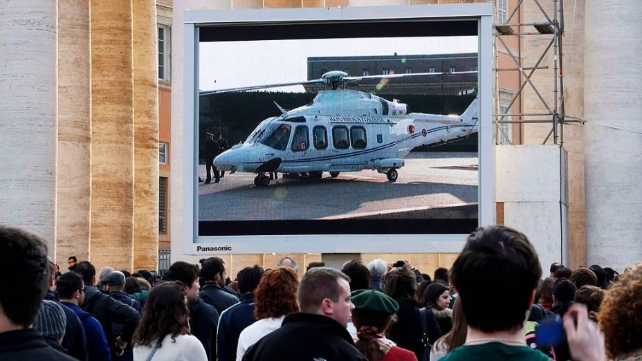 Fiéis assistem em um telão o helicóptero que levará o Bento XVI para a residência papal de verão, em Castelgandolfo