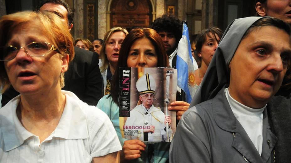 Fiéis argentinos comemoram proclamação de Jorge Mario Bergoglio como o novo papa, durante missa na Catedral de Buenos Aires