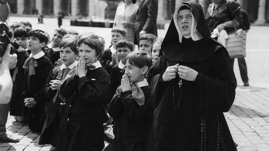 1963 - Uma freira com algumas crianças se ajoelham em oração na Praça de São Pedro à espera de notícias do papa João XXIII, que estava gravemente doente
