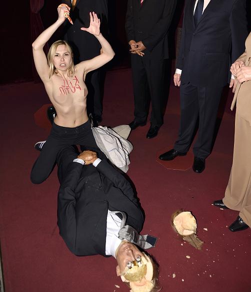 Uma ativista do grupo feminista Femen destrói uma estátua de cera do presidente russo, Vladimir Putin, no Museu Grévin em Paris