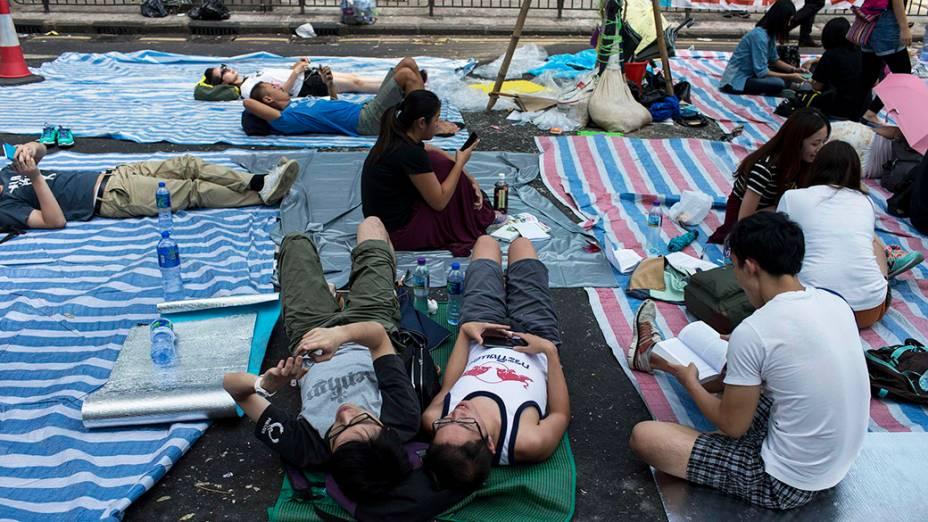 Manifestantes pró-democracia deitam em esteiras em baixo de tendas improvisadas no meio da rua, em Hong Kong
