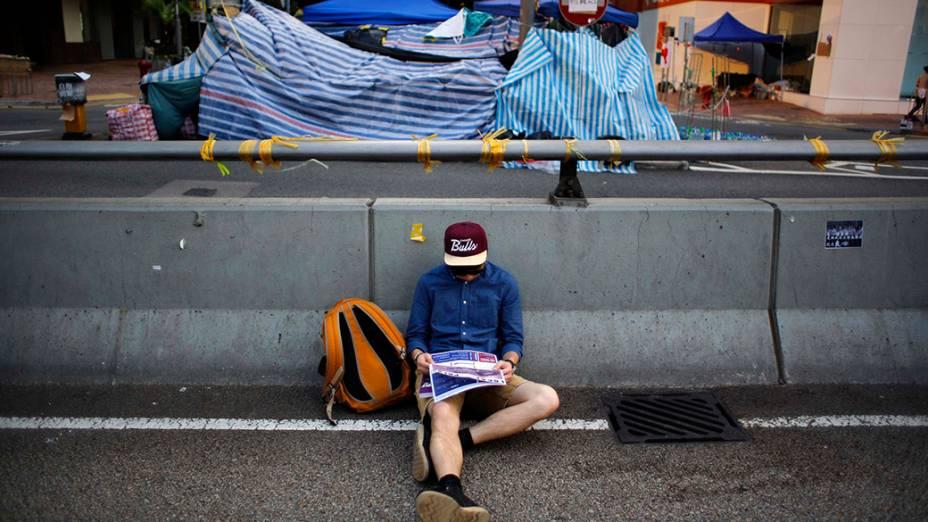 Um manifestante pró-democracia senta na rua em frente ao prédio do governo de Hong Kong