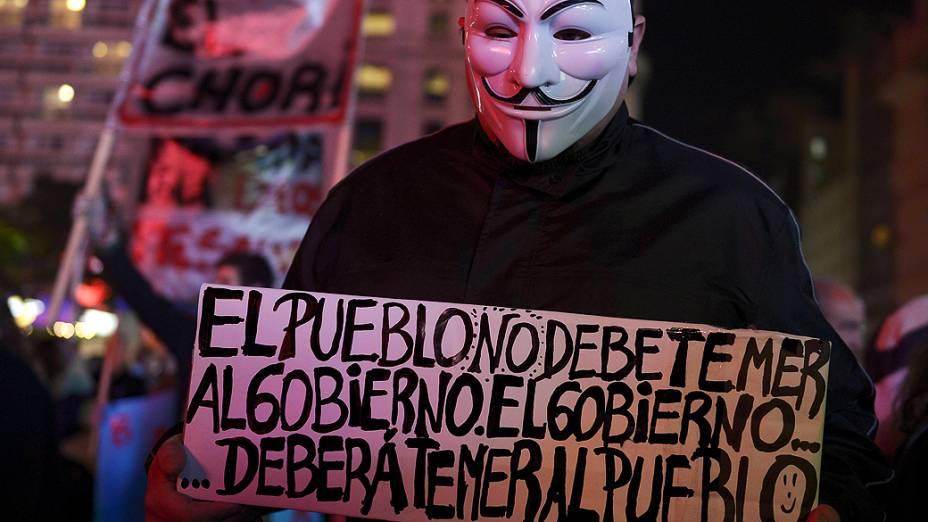 """Manifestante com máscara de V de Vingança segura cartaz com os dizeres: O povo não deve temer o governo. O governo deverá temer o povo""""."""