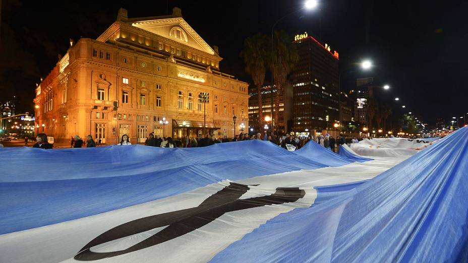 Bandeira gigante da Argentina com símbolo de luto é levada por manifestantes
