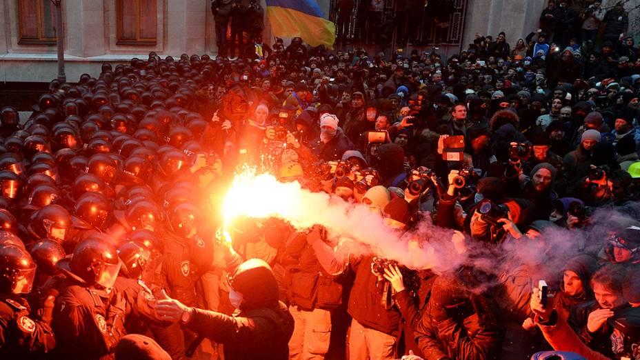 Manifestante segura um sinalizador na frente de policiais de choque durante confrontos perto do escritório presidencial, em Kiev, na Ucrânia