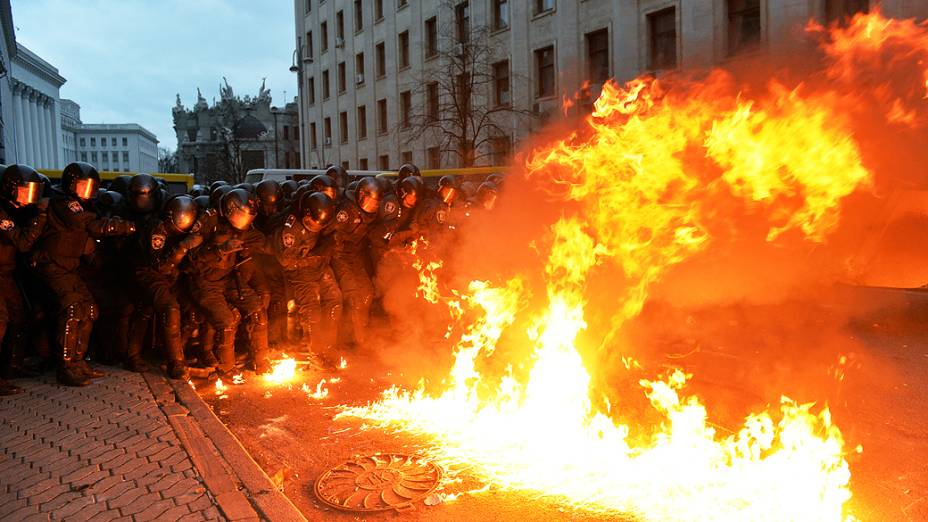 Um coquetel molotov explode em frente de membros da polícia de choque durante os confrontos com manifestantes, perto do escritório presidencial em Kiev, na Ucrânia