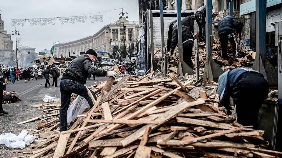 Pessoas recolhem madeiras na Praça da Independência em Kiev, na Ucrânia