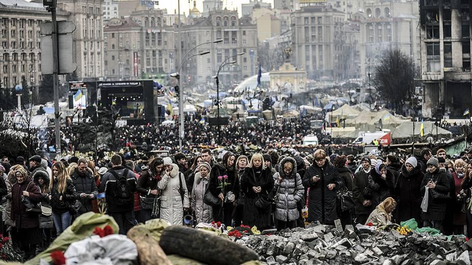 Pessoas visitam e lamentam diante dos destroços na Praça da Independência em Kiev, na Ucrânia