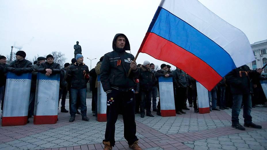 Homem segura a bandeira da Rússia durante um protesto em Crimeia, na Ucrânia em 01/03/2014