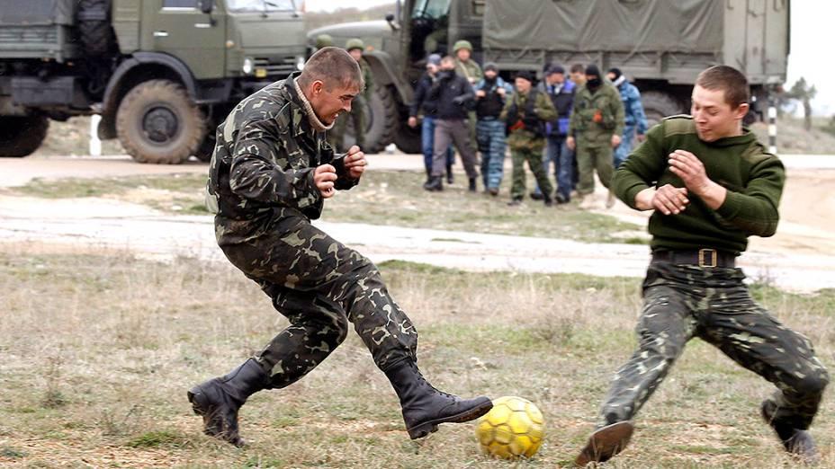 Soldados ucranianos jogam futebol próximo a veículos militares russos, na Crimeia