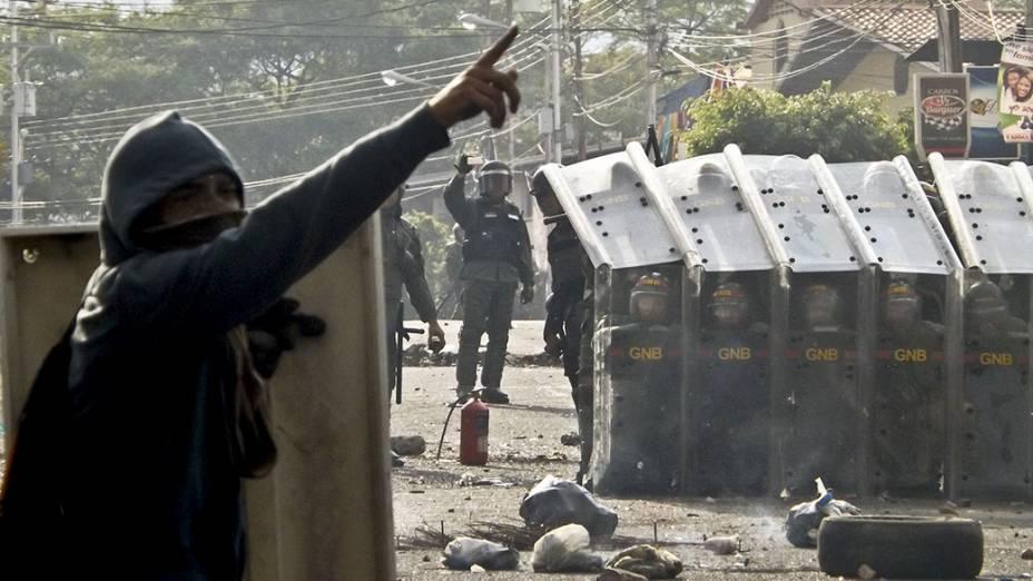 Manifestante em frente aos policiais da guarda nacional, durante protesto em San Cristóbal, na Venezuela - 21/02/2014