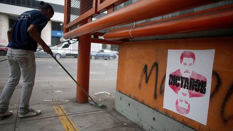 Cartaz do presidente da Venezuela, Nicolás Maduro, com a palavra Ditador é visto em um muro de Caracas, na Venezuela