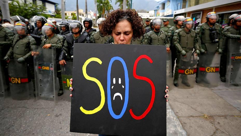 Manifestante segura um cartaz em frente a policiais da guarda nacional em frente a embaixada de Cuba em Caracas, na Venezuela - 25/02/2014