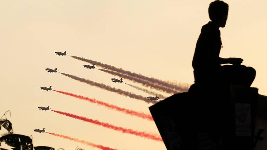 Silhueta de um homem ao pôr do sol enquanto jatos militares voam em formação sobre a praça Tahrir, no Cairo, nesta quinta-feira (4)