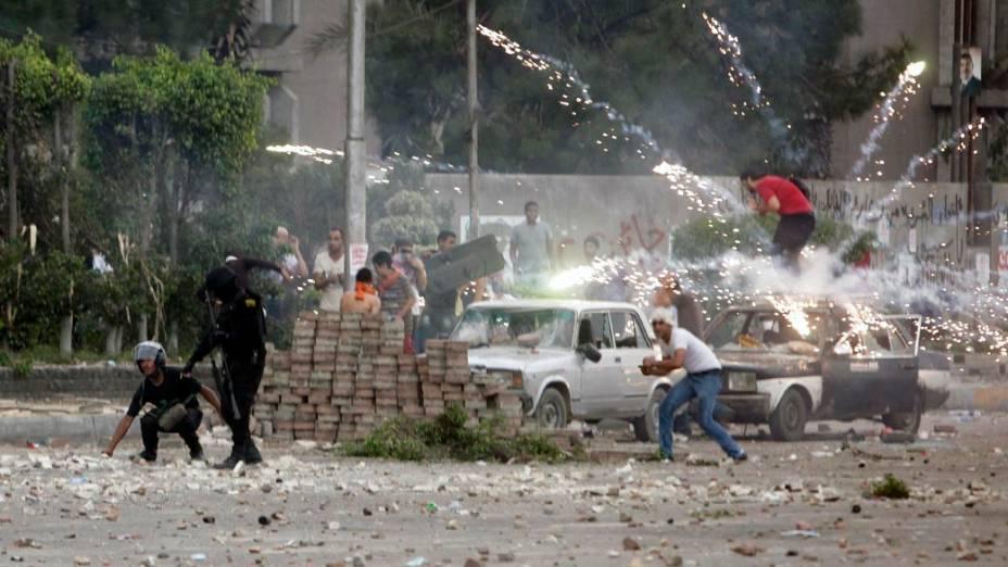 Fogos de artifício é lançado contra a polícia e manifestantes anti-Mursi na cidade de Nasr, no Egito