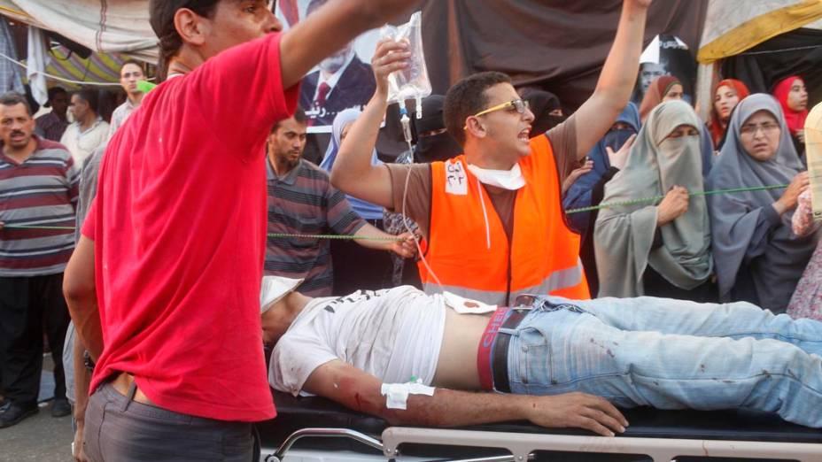 Partidários do presidente Mursi socorrem manifestante ferido durante confrontos com a polícia e opositores Mursi, em 27/07/2013