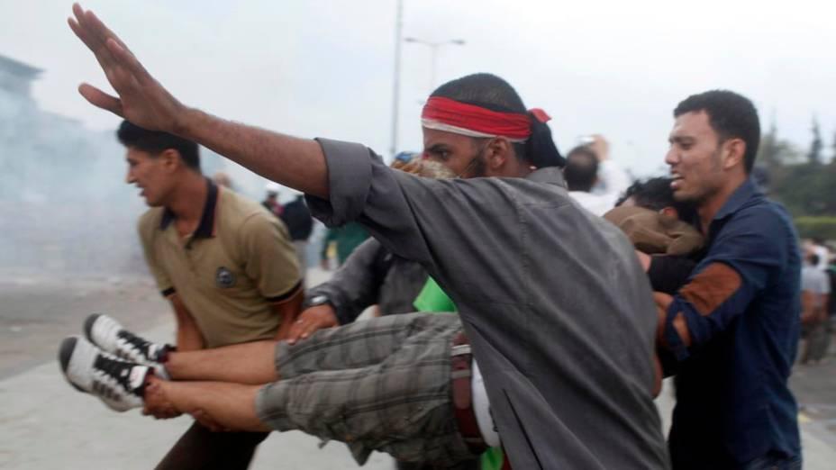 Partidários do presidente deposto Mursi carregam manifestante ferido durante confrontos com a polícia e opositores Mursi, na cidade de Nasr