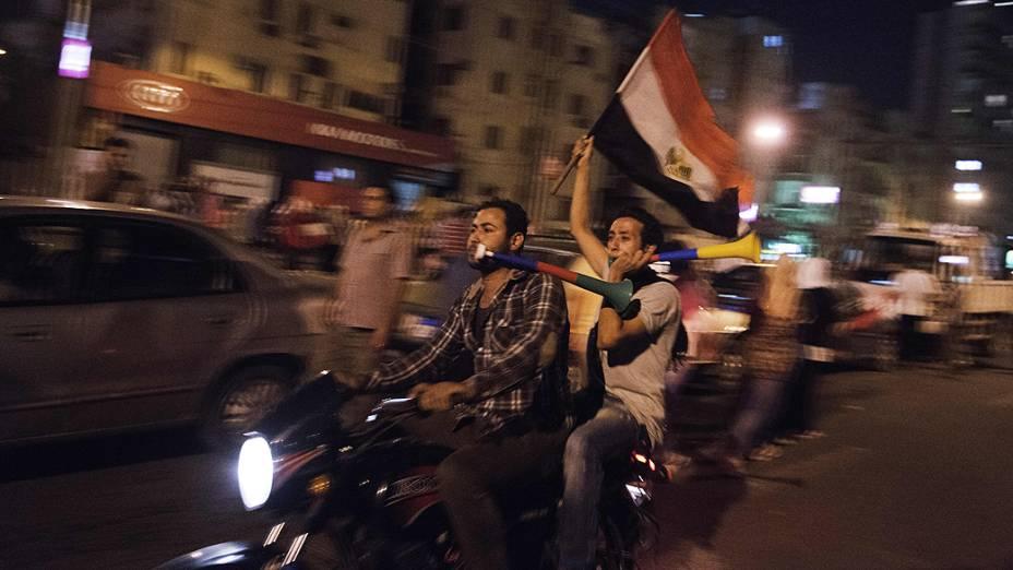 Homens em uma motocicleta carregam a bandeira egípcia durante um protesto pedindo a saída do presidente Mohamed Mursi, no Cairo, na segunda-feira 1º de julho