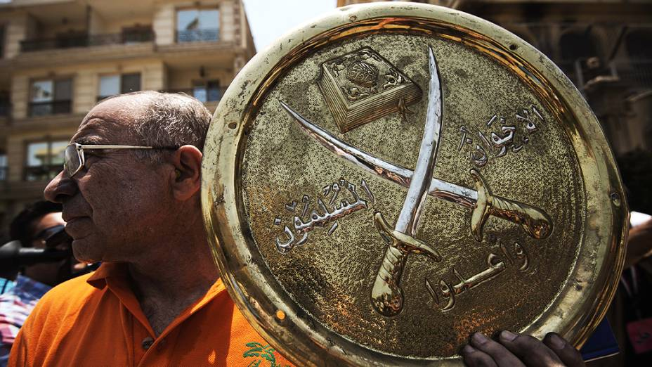 Homem segura uma placa com o emblema da Irmandade Muçulmana que foi retirada da sede do partido incendiada no distrito de Moqattam do Cairo, na segunda-feira 1º de julho