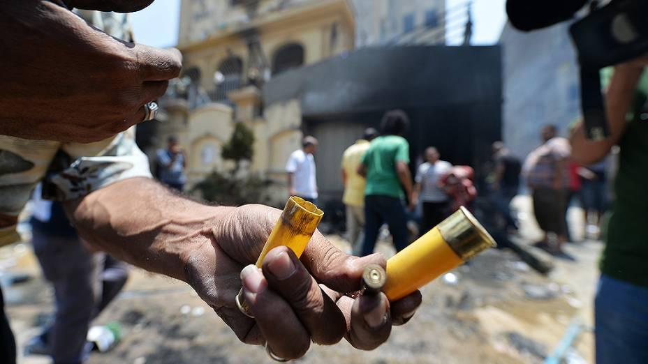 Egípcio mostra cartuchos de munição do lado de fora da sede incendiada, do partido da Irmandade Muçulmana no distrito Moqattam do Cairo, na segunda-feira 1º de julho