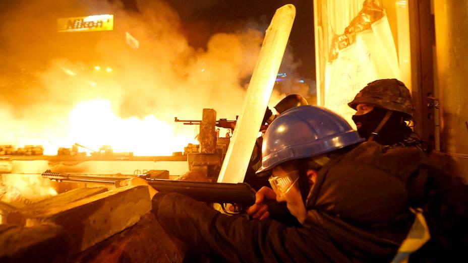 Manifestantes apontam suas armas para a polícia, durante protesto contra o governo em Kiev, na Ucrânia