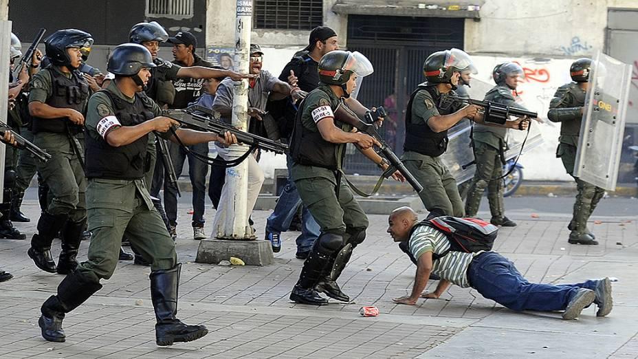 Manifestante fica deitado no chão, enquanto membros da Guarda Nacional se preparam para atirar durante um protesto da oposição contra o governo do presidente, Nicolás Maduro, em Caracas