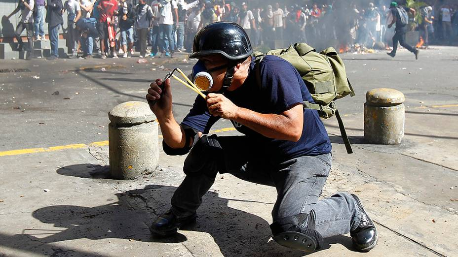 Manifestante usa um estilingue para atigir a polícia durante protesto contra o governo de Nicolás Maduro, em Caracas