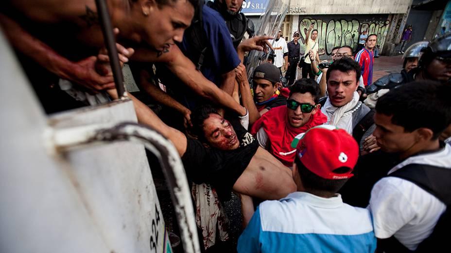 Estudante ferido com um tiro na cabeça é levado por outros manifestantes para o interior de um veículo da polícia em Caracas, Venezuela