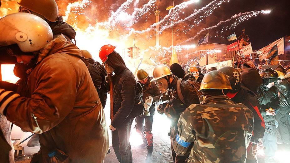 Fogos de artifício explodem perto de um grupo de manifestantes anti-governo durante confrontos com a polícia na Praça da Independência em Kiev