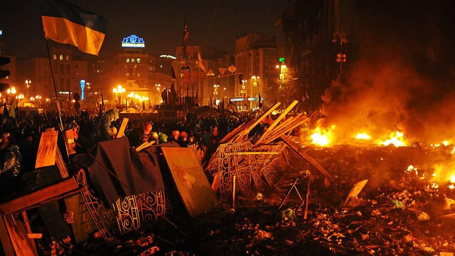 Grupo de manifestantes anti-governo permanece atrás de uma barricada durante confrontos contra a polícia nesta quarta-feira (19), na Praça da Independência, no centro de Kiev