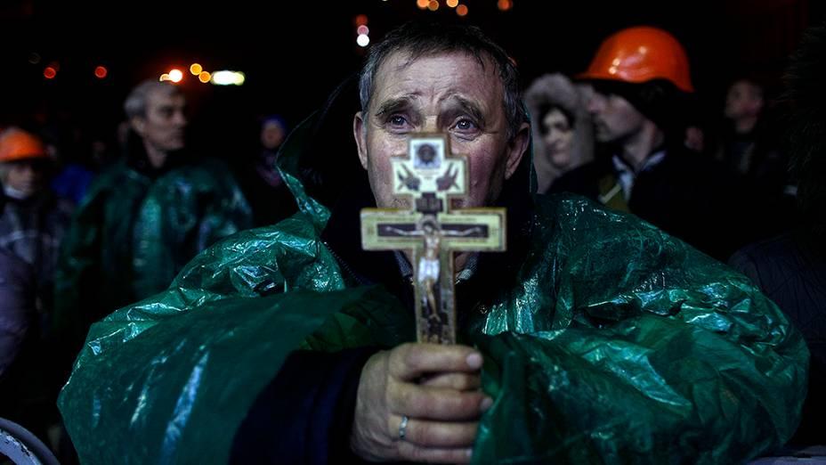 Manifestante anti-governo segura um crucifixo enquanto faz orações na Praça da Independência, em Kiev, na Ucrânia