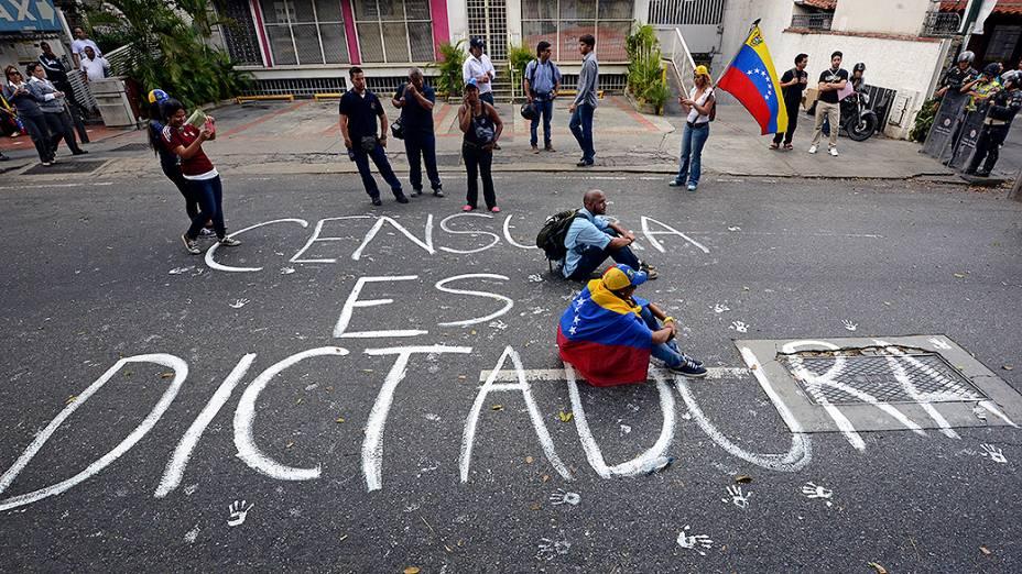 Estudantes sentam na rua sobre a frase A censura é ditadura, durante um protesto anti-governo em Caracas - (17/02/2014)