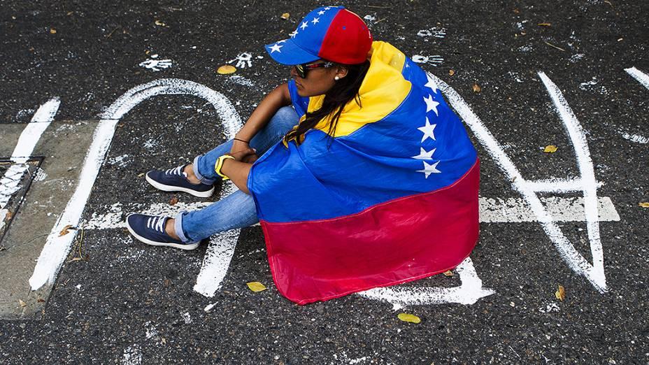 Manifestante com a bandeira da Venezuela em frente a um bloqueio de policiais durante protesto contra o governo do presidente Nicolas Maduro, em Caracas - (17/02/2014)