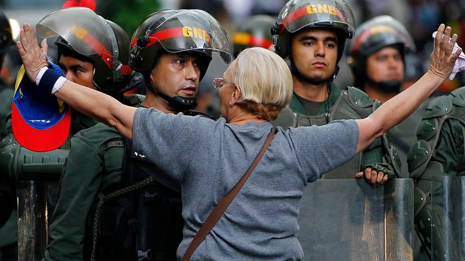 Manifestante da oposição se coloca em frente a uma barreira policial durante protesto contra o governo do presidente Nicolas Maduro, em Caracas