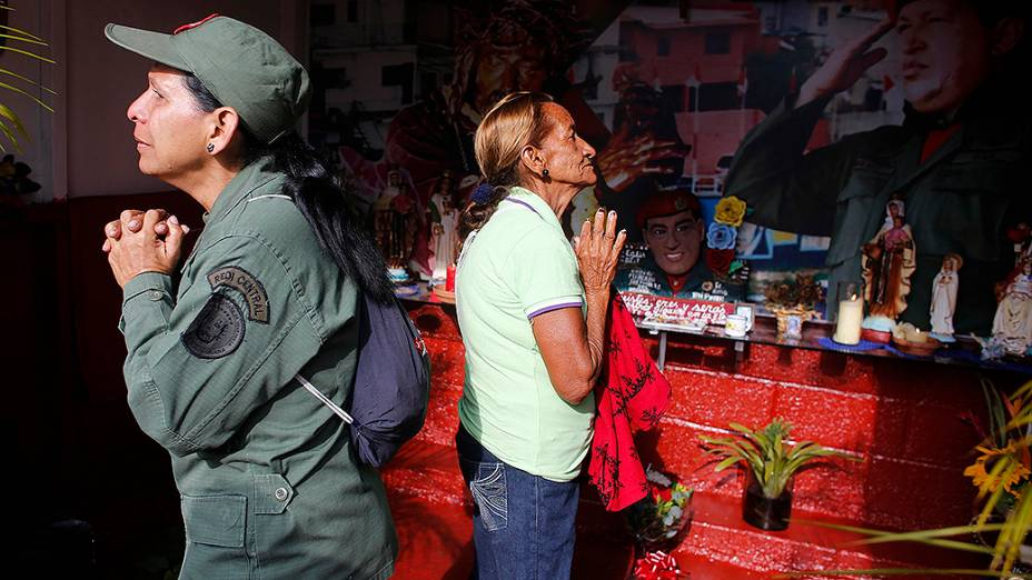 Uma militar e uma moradora do bairro de 23 de Enero, em Caracas fazem orações no aniversário de morte de Hugo Chávez
