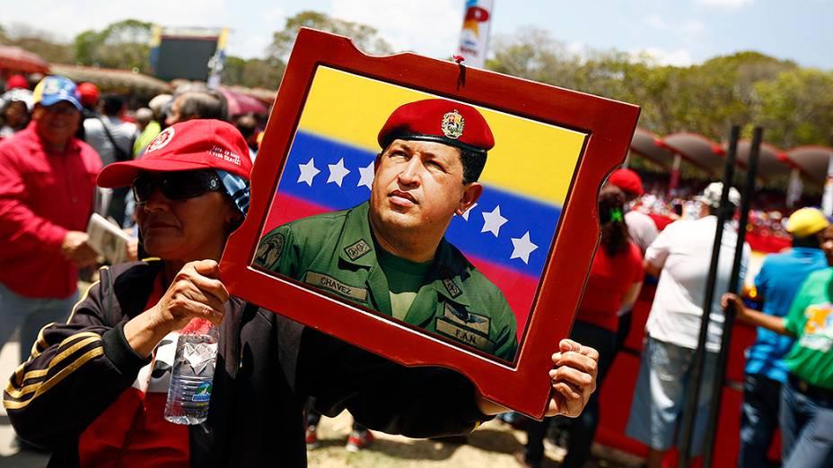 Mulher carrega um retrato de Hugo Chávez durante parada militar em homenagem ao aniversário de morte do ex-presidente venezuelano