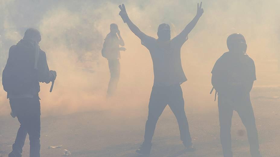 Estudantes venezuelanos caminham em meio a bombas de gás lacrimogêneo disparadas pela polícia durante um protesto contra o governo do presidente Nicolás Maduro, em Caracas - (12/03/2014)